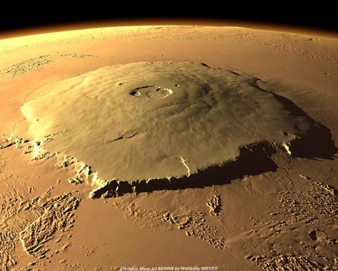 תמונת לווין של אולימפוס מונס שבמאדים, הר הגעש הגדול ביותר במערכת השמש – שגובהו גדול פי שלושה מגובה האוורסט. יתכן שפליטת הגזים הוולקניים, ובמיוחד גז החממה גופרית דו-חמצנית, גרמה, לפני כארבעה מיליארד שנה, להתחממות פני השטח של כוכב-הלכת.